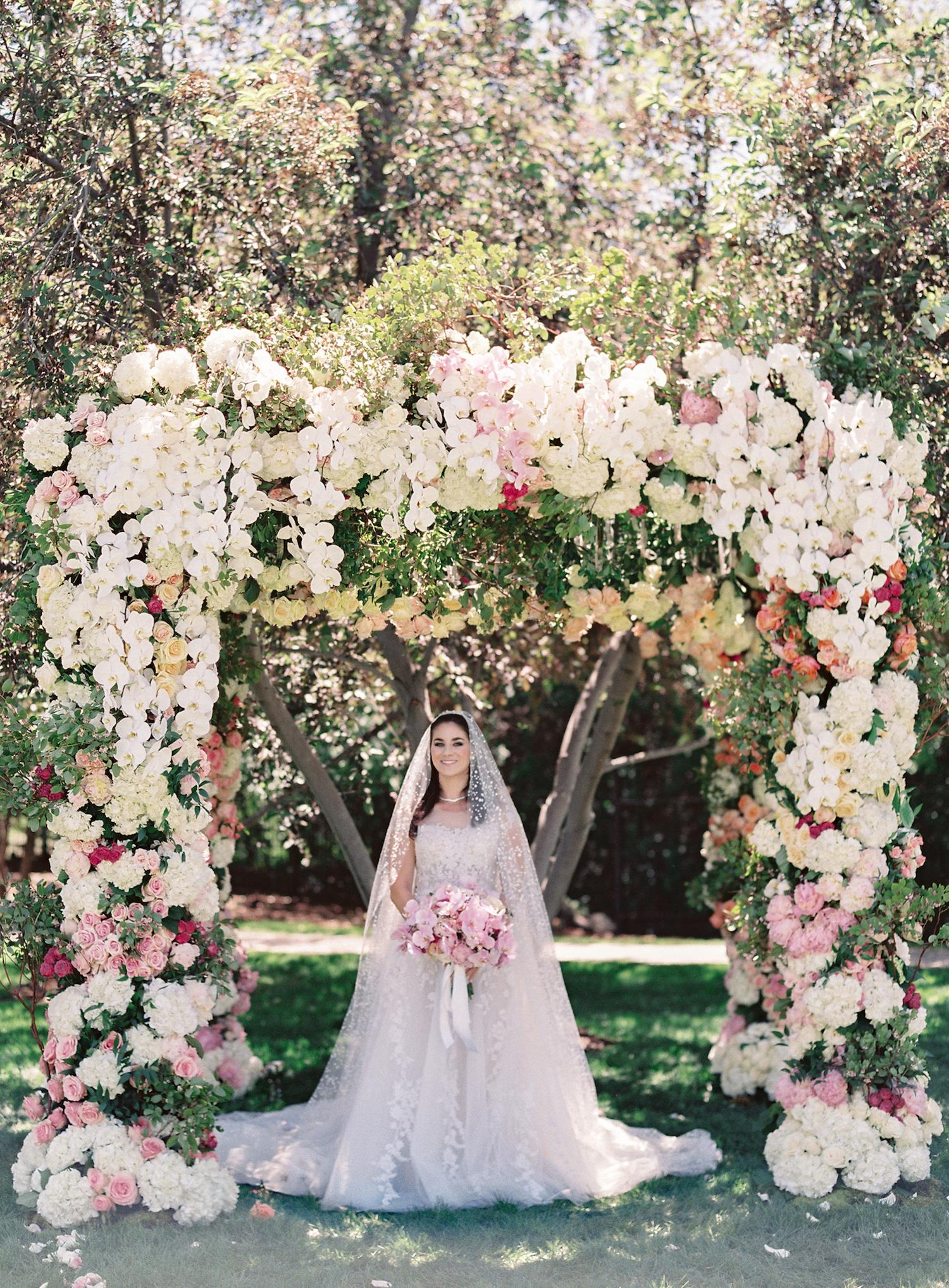 bride-under-lavish-floral-chuppah